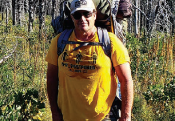 David Kacke standing in the woods in hiking gear.