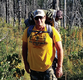 David Kacke standing in the woods in hiking gear.