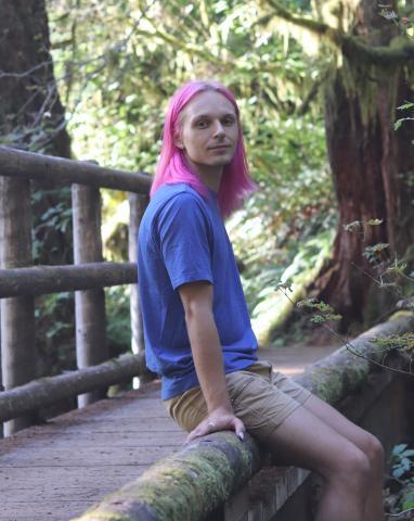 Matt sitting on a bridge in the forest.
